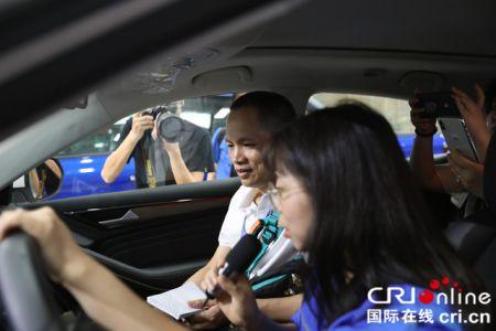 印尼《国际日报》记者陈浩光(左)体验配有智能语音功能的SUV 摄影 胡竹根