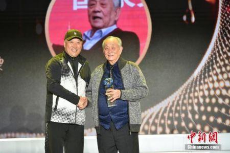 图为中国羽毛球队原总教练李永波为王文教献上奖杯。中新社记者 翟璐 摄