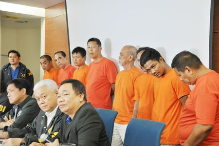 图为国调局官员昨天向媒体展示在三描礼斯省向河中倾倒有毒物品的9个人,包括两名华人。