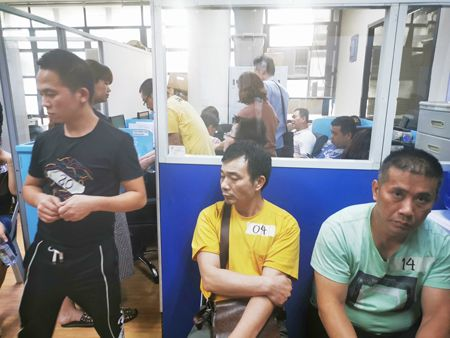 图为前天晚上在马尼拉市敦洛区商店內被移民局人员拘捕的中国人昨天在移民局接受核实身份。